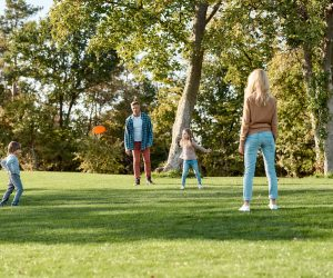 Full-length portrait of happy family of four playing with disc on a green meadow with grass. Family, kids and nature concept. Horizontal shot.