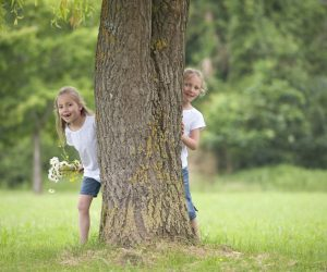 little girls playing hide and seek in the park