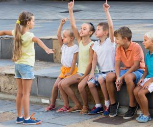 kids in school age playing charades outdoors