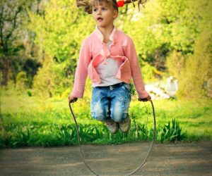 Beautiful little 6 years old girl jumping over the rope in the park on sunny summer day